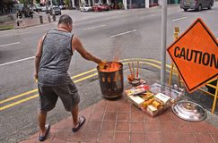 Singapore 28.08.2017. - Man with Sacrificial burning and offering on street on The Chinese Ghost Festival Spirit Festival. royalty free stock photography