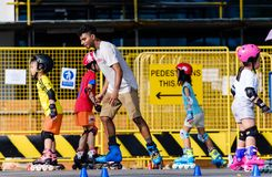 Singapore-23 MAR 2019:Roller skating class with senior teacher and little children in park royalty free stock photography