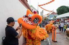 People in traditional costume perform the Chinese lion dance, Chinatown, Singapore. Singapore - March 24, 2018: A man takes a photo up close of performers in Stock Photos