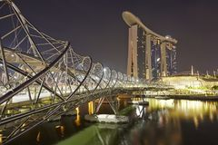 Singapore Marina Bay Sands Hotel and Helix Bridge. Panoramic view of Singapore Marina Bay Sands hotel and the unique helix bridge at night Royalty Free Stock Photos