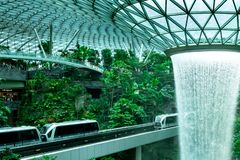 HSBC Rain Vortex, the world`s tallest indoor waterfall at Jewel Changi Airport. Green forest in the mall and skytrain. Iconic stock photo
