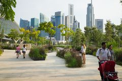 Singapore - May 1 2016: Park with people going for a walk against high building on background in Singapore.  Stock Photography