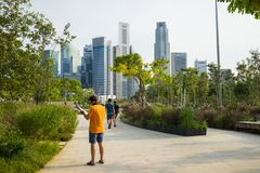 Singapore - May 1 2016: Park with people going for a walk against high building on background in Singapore.  Stock Image