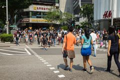 Singapore - May 1 2016: People crossing street in Orchard Rd, Singapore.  Royalty Free Stock Photos
