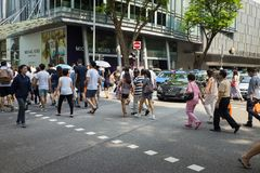 Singapore - May 1 2016: People crossing street in Orchard Rd, Singapore.  Royalty Free Stock Photo