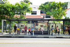 Singapore - May 1 2016: People waiting for bus at bus stop in Orchard Rd, Singapore.  Royalty Free Stock Image