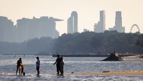 Leisure image of people enjoysthe beach with Singapore central district buildings royalty free stock image