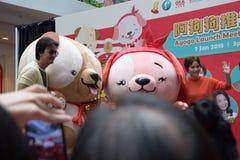 Singapore Mediacorp artister Chen Hanwei och Zoe Tay med maskot för det mån- nya året av hunden Arkivfoton