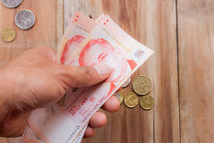 Singapore money in hand holding on wooden table background Stock Photo