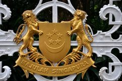 Singapore national emblem in brass metal. The national emblem of Singapore as seen on the gate of the Presidency. The central emblem of the coat of arms is a red Royalty Free Stock Image