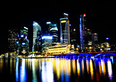 Singapore Night Skyline. Skyscrapers at night in Singapore with reflections on water Royalty Free Stock Photos