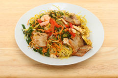 Singapore noodles in a bowl. Chinese meal, Singapore noodles in a bowl on a wooden tabletop royalty free stock photography
