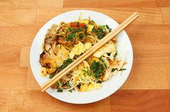 Singapore noodles in a bowl. With chopsticks on a wooden tabletop stock image