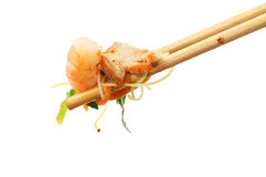 Singapore noodles in chopsticks. Chinese food, Singapore noodles held in chopsticks isolated against white stock photo