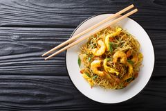 Singapore Noodles Mei Fun with shrimps, sausage, omelet and vegetables close-up on a plate. Horizontal top view. Singapore Noodles Mei Fun with shrimps, sausage royalty free stock photo