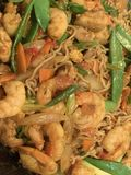Singapore Noodles with prawns and chicken. This is a Singapore style stir fry with prawns, chicken, snow peas, sugar snap peas, baby corn, curry powder, hoisin royalty free stock photography