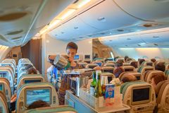 Flight attendant serve food and drinks. SINGAPORE - NOVEMBER 03, 2015: flight attendant serve food and drinks to passengers on board of Singapore Airlines Airbus Royalty Free Stock Image