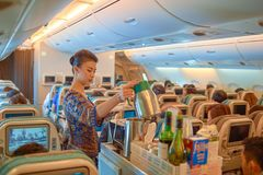 Flight attendant serve food and drinks. SINGAPORE - NOVEMBER 03, 2015: flight attendant serve food and drinks to passengers on board of Singapore Airlines Airbus Stock Images
