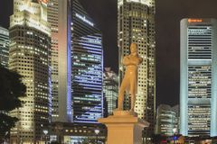 Raffles Landing Site by night. SINGAPORE - NOVEMBER 13,  2014: Statue of Sir Stamford Raffles a founder of the city at the Raffles` Landing Site with buildings Stock Photos