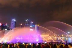 Singapore - 13 Oktober 2018 Affärsområde av skyskrapor på nattetid och springbrunnshowen royaltyfri bild