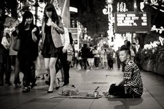 Beggar and rich woman in a shopping district in Singapore royalty free stock images