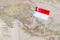 Singapore flag pin on a world map. Singapore paper flag pin on an ancient world map. Officially the Republic of Singapore, it is a sovereign city-state and royalty free stock image