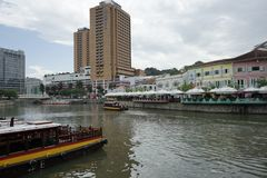 A bridge at Clarke Quay with a hotel and skyscrapers in the background. Stock Image