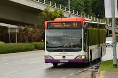 Singapore SBS public bus on road approaches bus stop Stock Photos
