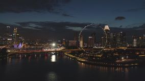 Singapore - 25 September 2018: Singapore cityscape panorama by night with farris wheel behind the river. Shot. Aerial. Singapore cityscape panorama by night with stock footage