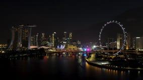 Singapore - 25 September 2018: Den flyg- sikten av storstaden med många ljus, molnig himmel och ferris rullar på natten skjutit royaltyfria bilder