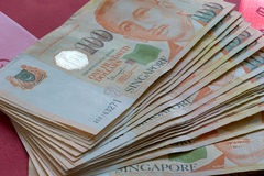 Singapore SGD One Hundred Dollar Stack Closeup. Singapore SGD 100 One Hundred Dollars Stack Fan Out on Red Packet Background Stock Images