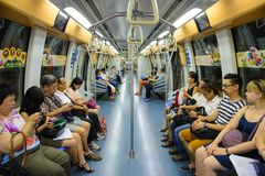 Singapore, Singapore - August 19, 2015 : Indoor view of people in a rail commuters ride a crowded Mass Rapid Transit MRT train.  Royalty Free Stock Images