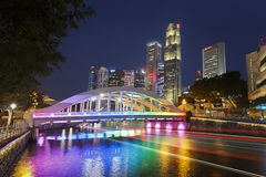 SINGAPORE, SINGAPORE - CIRCA 2016: Elgin Bridge Illuminated in Rainbow Colours. The rainbow colourd Elgin Bridge with downtown Singapore in the background Royalty Free Stock Images