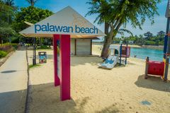 SINGAPORE, SINGAPORE - FEBRUARY 01, 2018: Gorgeous blue day and unidentified people walking in the beach and informative. Sign with pink columns in Palawan Royalty Free Stock Photography