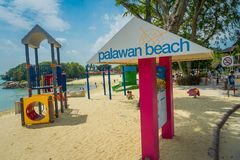 SINGAPORE, SINGAPORE - FEBRUARY 01, 2018: Unidentified people walking in the beach and informative sign with pink. Columns in Palawan Beach at Sentosa Island Stock Images