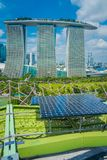 SINGAPORE, SINGAPORE - JANUARY 30, 2018: Close up of solar pannel with a beautiful landscape of three towers of the Stock Photos