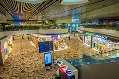 SINGAPORE, SINGAPORE - JANUARY 30, 2018: Above view of informatives signs, stores, electric stairs and people walking. Inside of the Singapore Changi Royalty Free Stock Image