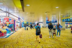 SINGAPORE, SINGAPORE - JANUARY 30, 2018: Close up of unidentified people walking and waiting in a lounge located at the. Enter of Singapore Changi Airport Royalty Free Stock Photo