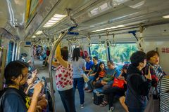 SINGAPORE, SINGAPORE - JANUARY 30, 2018: Indoor view of people in a rail commuters ride a crowded Mass Rapid Transit MRT. Train through the city centre, has a Royalty Free Stock Image