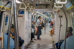 SINGAPORE, SINGAPORE - JANUARY 30, 2018: Indoor view of people in a rail commuters ride a crowded Mass Rapid Transit MRT. Train through the city centre, has a Stock Images