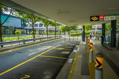SINGAPORE, SINGAPORE - JANUARY 30, 2018: Outdoor view of parking area at outside of a building with unidentified people. Walking in the sidewalks at Mass Rapid Royalty Free Stock Photo
