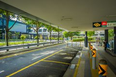 SINGAPORE, SINGAPORE - JANUARY 30, 2018: Outdoor view of parking area at outside of a building with unidentified people. Walking in the sidewalks at Mass Rapid Stock Image