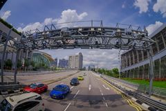 SINGAPORE, SINGAPORE - JANUARY 30. 2018: Outdoor view of some cars crossing under a metallic structure in a highway with. A residential condominium building Royalty Free Stock Photography