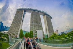 SINGAPORE, SINGAPORE - JANUARY 30, 2018: Outdoor view of unidentified people using an electric stairs with a beautiful. Three towers of the Marina Bay Sands Royalty Free Stock Photos