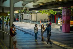 SINGAPORE, SINGAPORE - JANUARY 30, 2018: Outdoor view of unidentified people walking in the sidewalks close to at Mass. Rapid Transit MRT train through the city Royalty Free Stock Photography
