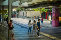 SINGAPORE, SINGAPORE - JANUARY 30, 2018: Outdoor view of unidentified people walking in the sidewalks close to at Mass. Rapid Transit MRT train through the city Royalty Free Stock Photos