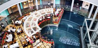 Singapore, Singapore - June 29, 2018: Top view people eating food at restaurant and tourist walking and shopping in Marina shoppin stock photography