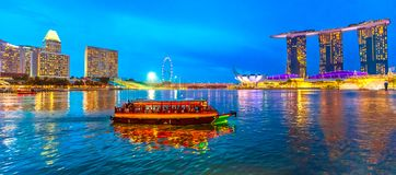 Singapore Skyline at evening. Panorama of Singapore buildings, skyscrapers and ferris wheel reflected in the sea. Tourist boat sails in the bay at evening stock photos