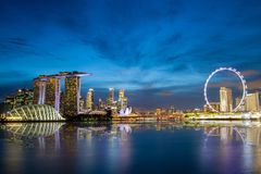 Singapore Skyline at Marina Bay During Sunset Blue Hour. Showing skyscrapers in downtown and giant ferris wheel in motion Stock Image