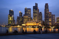 Singapore Skyline and People at Twilight. Singapore skyline at twilight. Couples and tourists sitting on the sea wall, watching the lights come on. Slight motion Stock Photos